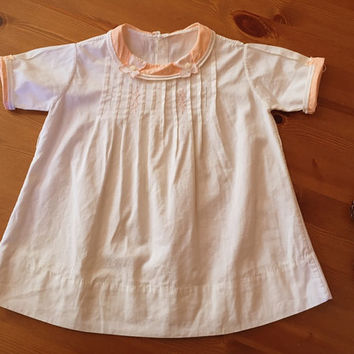 Adorable toddler dress/smock. Peachy-pink collar and cuffs. 1940s.