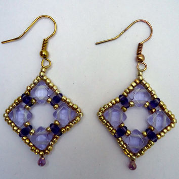 Dangle earrings in shades of lilac super duo and silky duo beads surrounded with gold seed beads and a hanging teardrop bead.