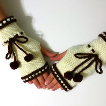 Knitted fingerless mittens in beige and brown colors, wrist warmers decorated with pompom, winter accessory.