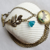 Round locket with butterfly on front cover adorned with blue flower charm and bronze accents