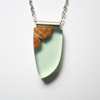 Small tooth shaped pendant / necklace from light mint green resin and Australian wood with a silver tone tube on a rhodium-plated chain