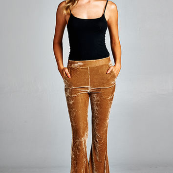 These stretchy soft velvet fabrication pants,featuring taper cut in the knee, flare bell bottom, two side pockets, with an elastic waist band. Unlined. Pair with wedge booties, fringe top and floppy hat.