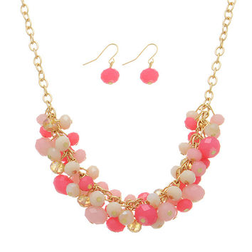 Gold tone necklace set featuring dangling pink glass stone and topaz beads