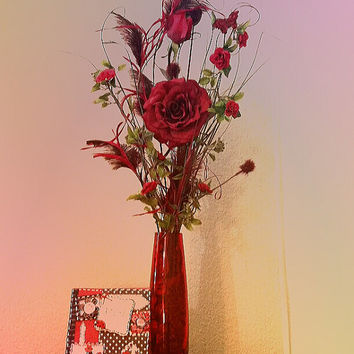 Handmade floral arrangement. Beautiful long stem red roses set in a red tinted glass vase filled with rose potpourri .