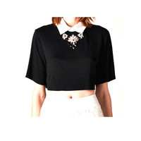 Featuring a man's shirt cotton-white-collar-neckline front and back with keyhole cutout at back, button closure, relaxing fit, cropped constructions, short sleeves. wear with statement rhinestone & beaded necklace and pair with high waist leather shorts.