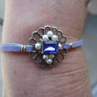 Beaded lilac leather bracelet with a purple emerald cut swarovski crystal surrounded by faux pearls on an antique background and  extension.
