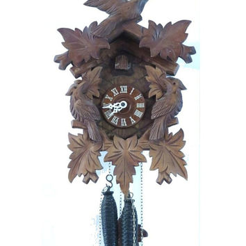 Black forest cuckoo clock. Working mechanical clock. Wood wall clock. Carved wood clock. Three birds and leaves. Vintage.