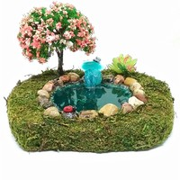 Fairy garden miniature stone koi fish pond with shell waterfall and blossoming tree.