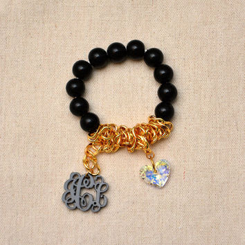 Vine Interlocking Monogram hanging on stretch string Bracelet made of black beads and gold plated chain