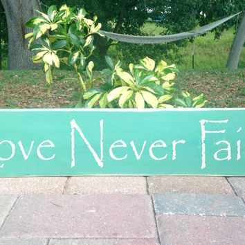 18x4 Love Never Fails Wood Sign