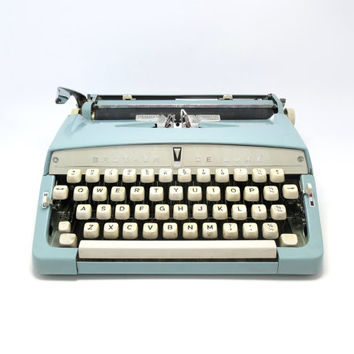 1960s Baby Blue Brother Deluxe Typewriter. In Good Condition. Includes Portable Carry Case and Ribbon.