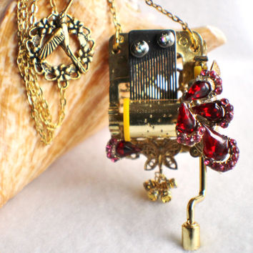 Hand crank music box pendant, music box movement adorned with vintage rhinestone jewelry.