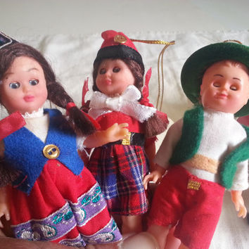 4 vintage folk dolls . international ornament dolls . vintage doll ornaments . vintage dolls in plastic tubes . small international dolls