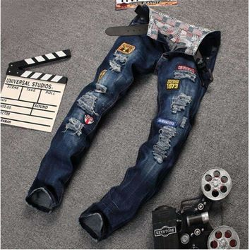 The new spring blue cloth personality Metrosexual hole patched jeans embroidery badges denim trousers