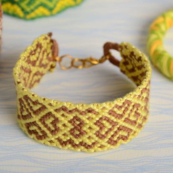 Handmade colored woven wide friendship bracelet made of floss threads yellow with beige