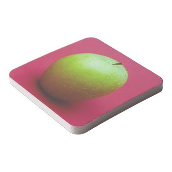 Green apple on red background square paper coaster