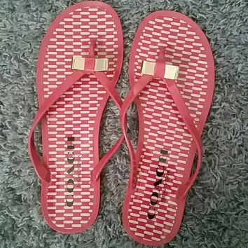 Pink COACH jelly flip flops with gold bows