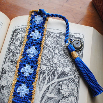 Crochet bookmark with a long tassel, light blue, blue, and gold, charms on the tassel, moon and stars