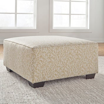 Ayanna Nuvella square ottoman upholstered in a smooth sand polyester fabric with a white coral motif pattern