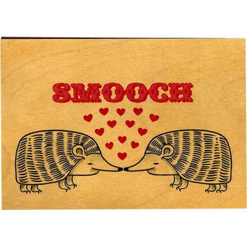"""Wood folding card comes with tattoo print with """"Smooch"""" written on natural wooden card, perfect for valentine's day, comes in it's own cardstock holder, packaged in a clear sleeve."""
