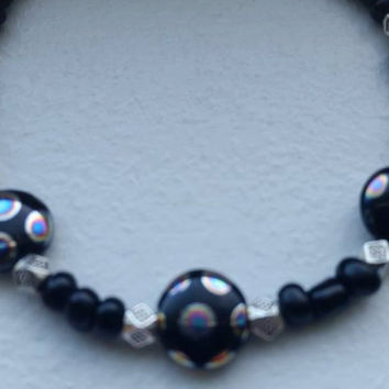 Hand beaded bracelet, black, silver and metallic rainbow colored beads.