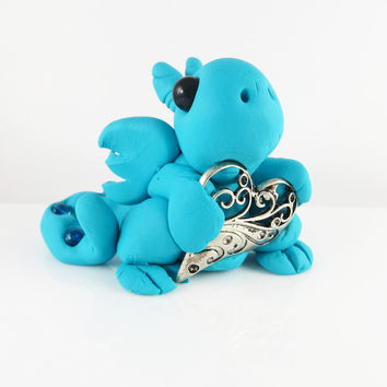 Polymer clay blue dragon with a filigree heart