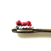 baby demon sleeping on a needle hole. Amazing micro sculpture ,4mm size, details only through lens