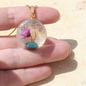 Ikebana inspired light purple flower in real turquoise vase, secret planet pendant with layered intricate golden adornments encased in resin