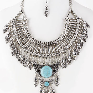 Featuring turquoise stone accents, bib construction, rhinestones & gemstone accents, textured charms, and finished with adjustable lobster hook closure. Necklace includes matching earrings. Lead and nickel free.