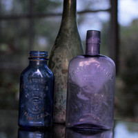 Set of three antique colored and iridescent glass bottles