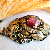 Dragon pendant with layers of bronze rings and floral filigree, surronding a dragons breath glass cabochon.