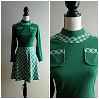 1960's green knee length A line dress with front pockets and plaid skirt and trim. long sleeved , Size medium