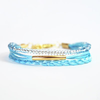 Blue satin cord bracelet with gold tube, braid and blue beads.