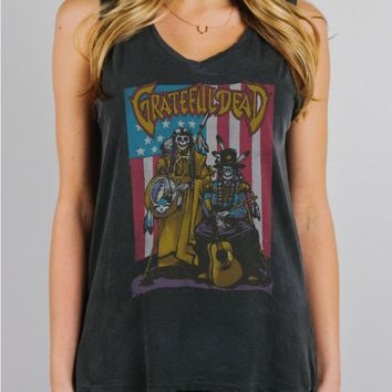 This super soft Grateful Dead tan top features relaxed Fit Piece-dyed construction with Grateful Dead graphic on front of tank top, sleeveless design, v-neckline, and flare bottom hem. Pair with distressed denim, lace maxi skirt and sandals.