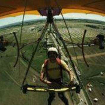 A Man Flies In A Hang Glider Powered By Two Chain Saw Engines
