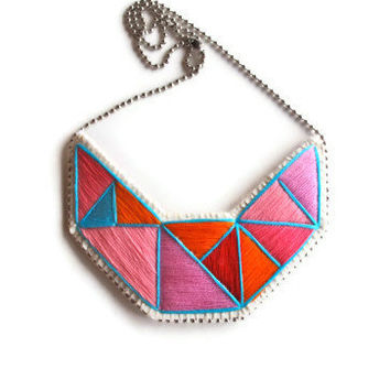 Embroidered statement necklace in bright neon pinks orange red and blue in a dramatic geometric design