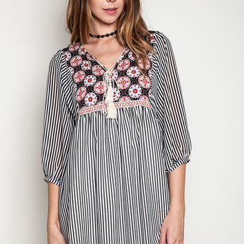 This flowy fit-and-flare dress features a round neckline with slit and self-tie tassel rope straps, circle patter at yoke from front and back, black and white striped print throughout, semi-sheer three quarter dolman sleeves, two side of pockets, pleated d