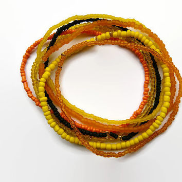 seed bead bracelet, friendship bracelet. Set of 7. Stretch, Orange, yellow black, different kinds of beads.