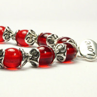 Stretch charm bracelet. Red bead bracelet. Red glass beads, silver plated bead caps.  Sterling silver love charm. CarolMade