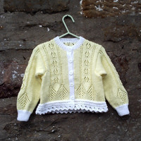 "Hand knitted girl's yellow lacy patterned cardigan with white trim. 22"" chest"