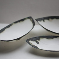 Stoneware fine bone china bowl with black rims resembles a small boat.