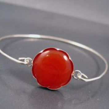 Thin bangle with a round red Agate gemstone by DvoraSchleffer