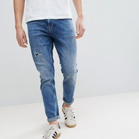 ASOS Tapered Jeans In Dark Wash With Rip & Repair at asos.com