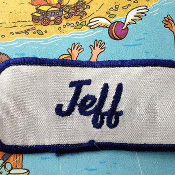 """Jeff. An off white work shirt patch that says """"Jeff"""" in dark blue script"""
