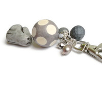 A sparkley grey hare gazes at an exceptionally close crater covered wooden moon bag charm, purse clasp, key chain, animal