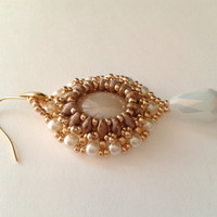 handmade beadwoven earrings of a beige  glass cabochon