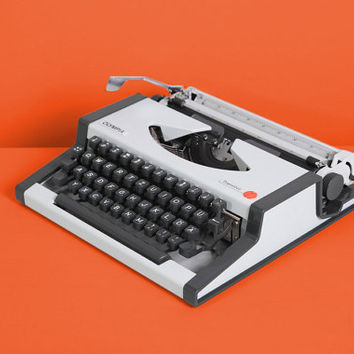 1970s Olympia Traveller Typewriter. Excellent working condition. Portable. Gray. Black and white. Remarkable design. Case.