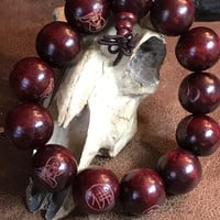 Native wooden beads in deep cranberry colors with tribal signs of prosperity on each beaded bracelet