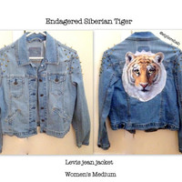 Siberian Tiger. One of our endangered big cats. Light denim Medium with spikes and studs. Women, teen fashion. Clothing.