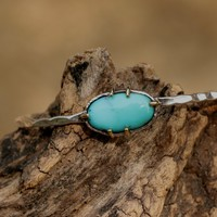 Dainty silver bangle bracelet with turquoise gemstone in silver and brass setting